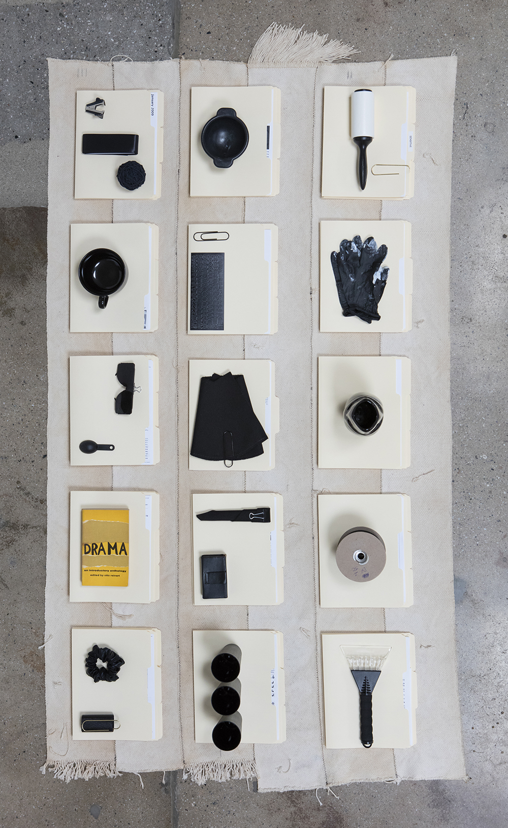 Amanda Ross-Ho and Diedrick Brackens. <em>Untitled Floor Arrangement (DRAMA)</em>, 2017. Handwoven cotton rugs, manilla folders, sensitive documents, labels, lint roller, black nitrile gloves, black vase, double fold bias tape (roll), ice scraper, plastic salsa bowl, oversized black paper clip, vinyl letters, material test with oversized black paper clip, material test with binder clip, camera case, three black owl glasses origin unknown, staple remover, satin seam binding, yarn ball, black mug, sunglasses, measuring spoon, DRAMA book, black scrunchie, and material test with oversized gold paper clip, 11 1/2 x 81 x 44 inches