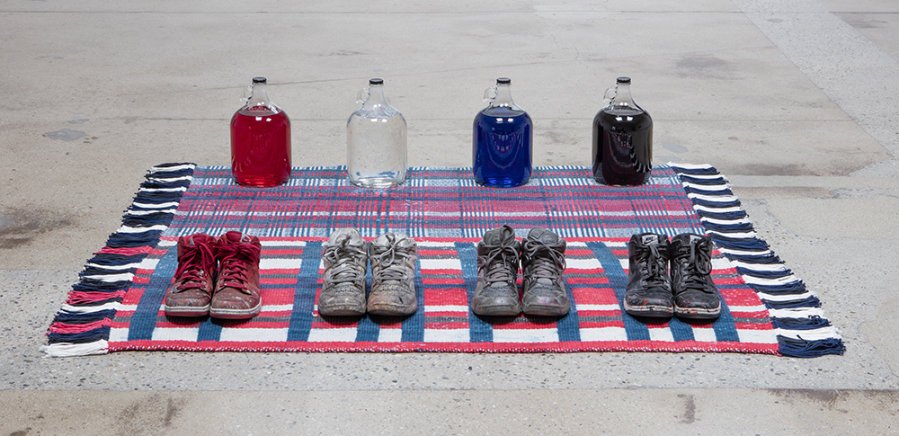 Amanda Ross-Ho and Diedrick Brackens. <em>Untitled Floor Arrangement (300 bucks would save my life)</em>, 2017. Handwoven cotton rugs, glass jugs, Procion dyes, Nike Dunks, and Reebok Pumps, 12 1/4 x 64 1/2 x 48 inches