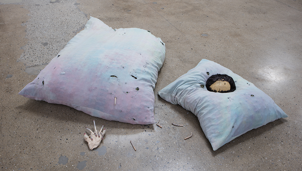 Lila de Magalhaes and Roni Shneior. <em>Close the Door Behind You</em>, 2017. Clay, resin, acrylic, dyed fabric, silver thread, hay, wig, and cigarettes, 16 x 80 x 72 inches