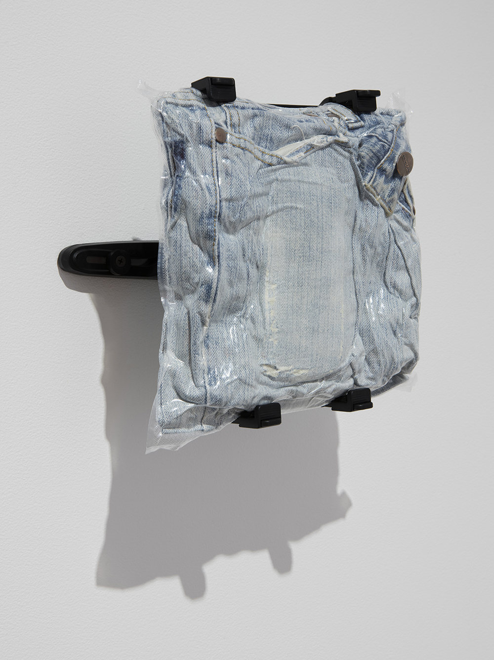 <em>Denim #4</em>, 2017. Vacuum packed jeans, tablet wall mount, 9 1/2 x 10 x 5 1/2 inches