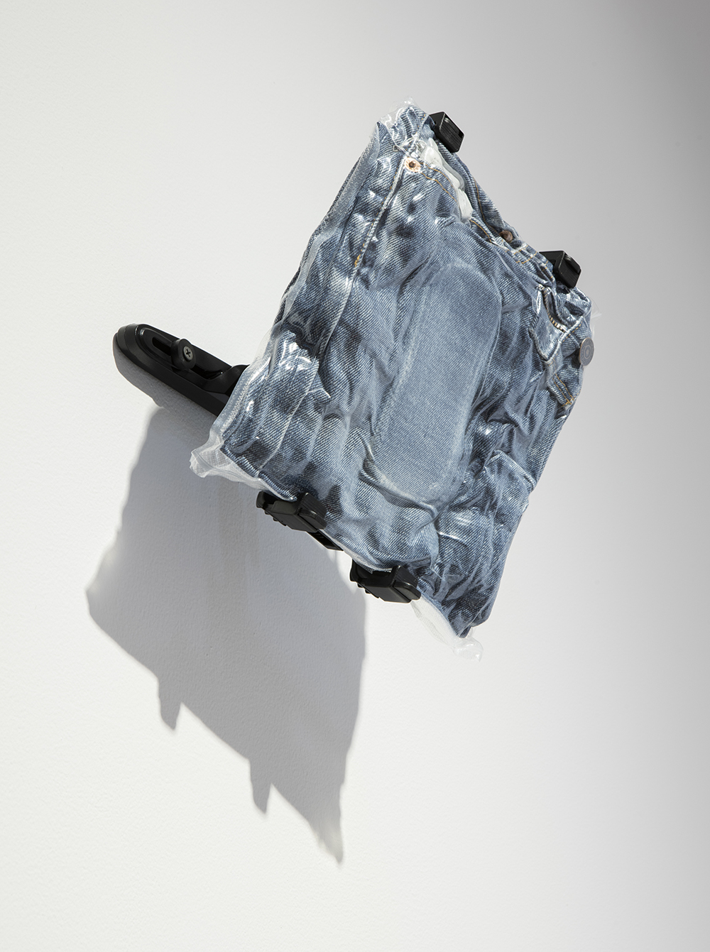 <em>Denim #5</em>, 2017. Vacuum packed jeans, tablet wall mount, 9 1/2 x 10 x 5 inches