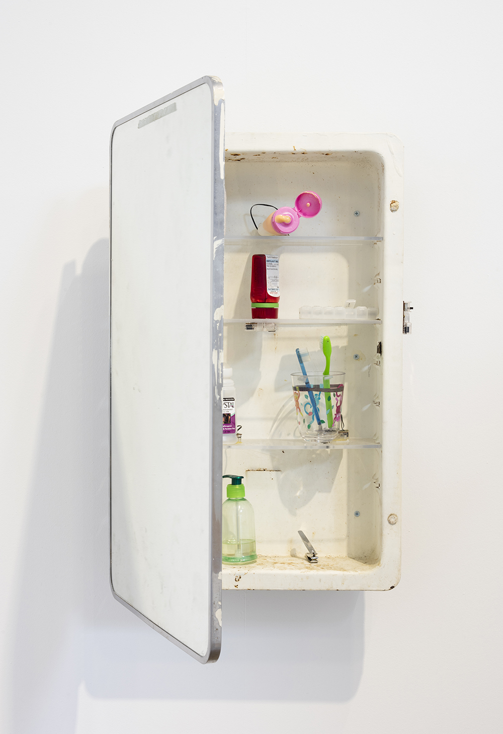 Tim Hawkinson. <em>World Clock</em>,  2012. Medicine cabinet, ace bandage, lotion bottle, prescription medicine bottle, dental floss, deodorant, toothbrushes, plastic cup, pump soap bottle, nail clipper and clock motors, 25 1/2 x 16 x 21 inches (64.8 x 40.6 x 53.3 cm)