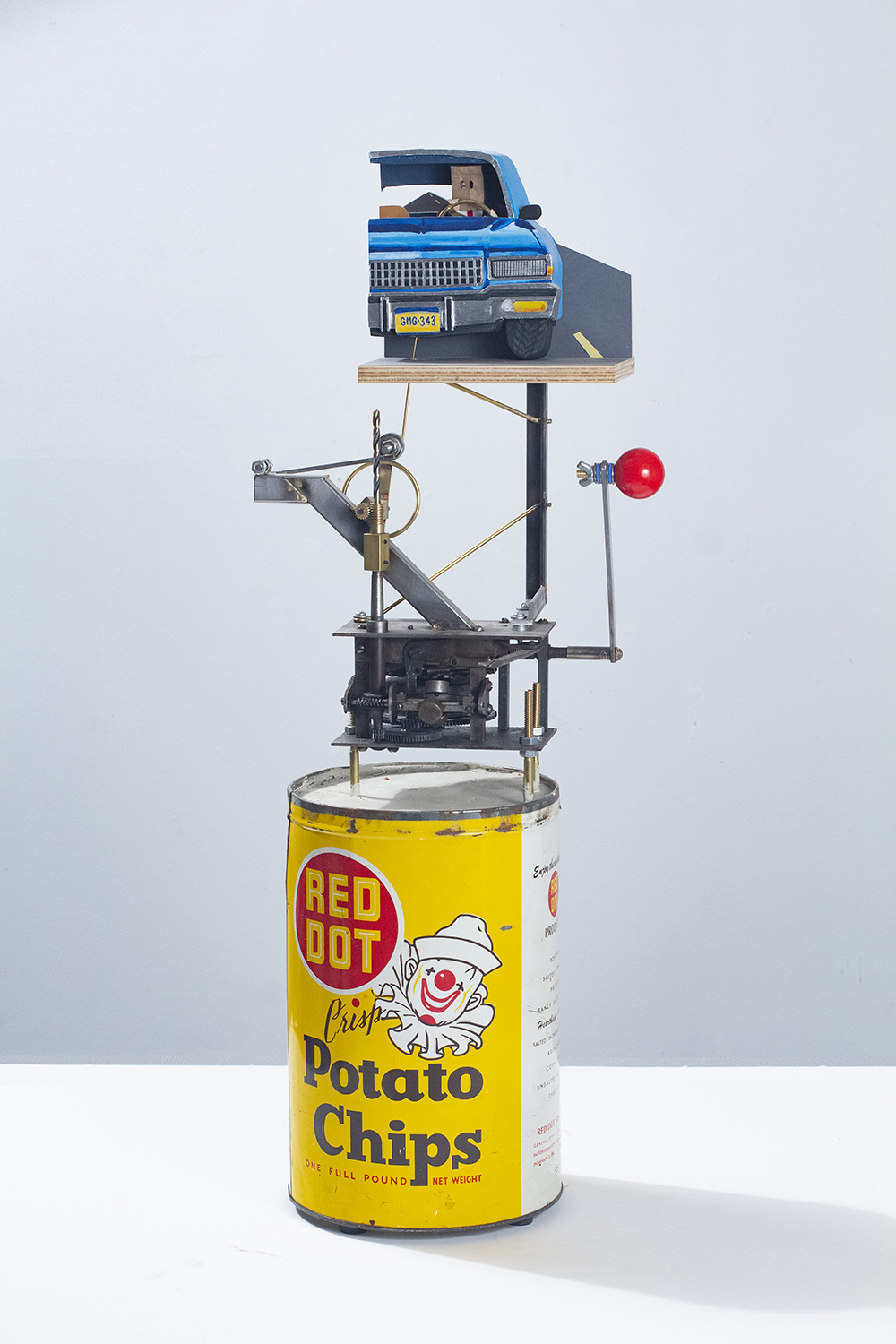 Nick Doyle. <em>Executive Toy: The Lonely Road</em>, 2019. Concrete, vintage tin, steel, brass, arcade game joystick, plywood, hardware, sandpaper, flashe, silica bronze, paper bag, skateboard bearing, denim, paper, cotton and phonograph motor, 28 1/2 x 11 1/2 x 7 inches (72.4 x 29.2 x 17.8 cm)