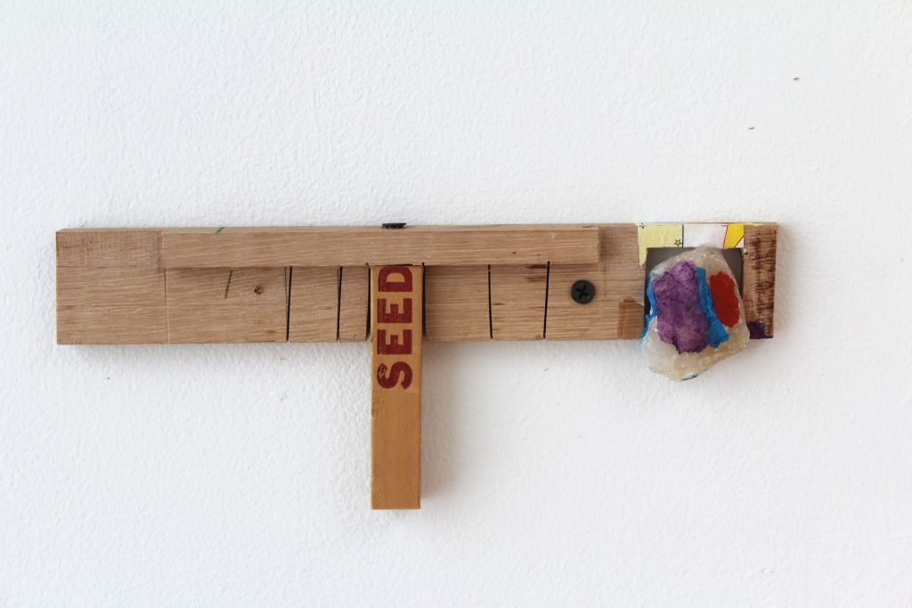 Kevin McNamee-Tweed.<em> Seeds Shelf</em>, 2019. Wood with affixed quartz, yardstick, and newsprint, 3 3/4 x 9 3/4 x 1 inches (9.5 x 24.8 x 2.5 cm)