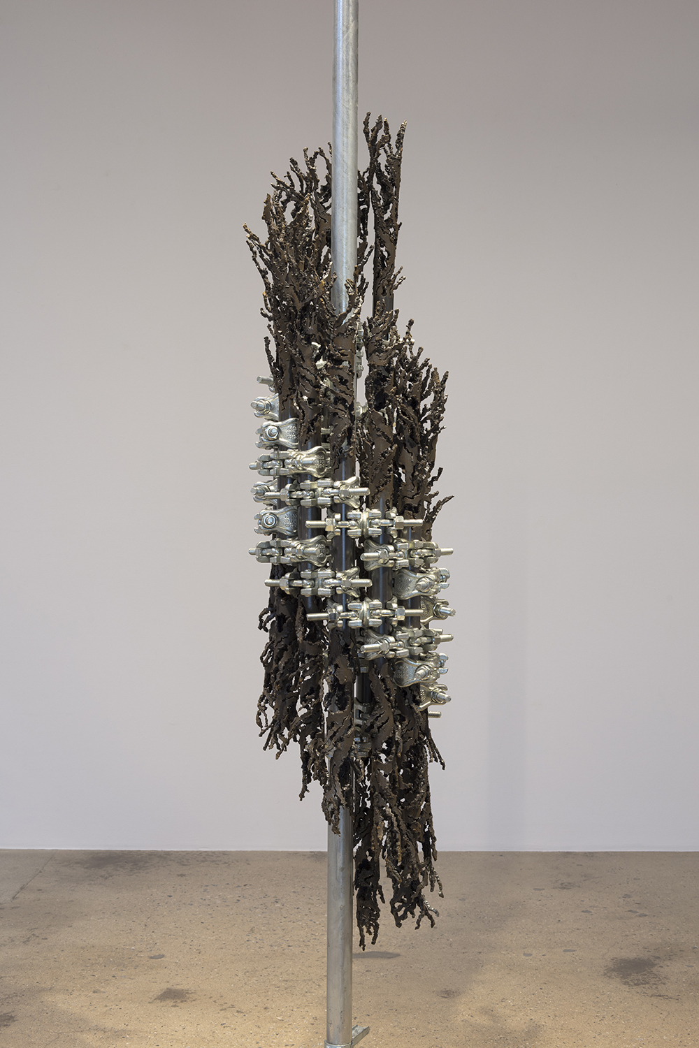 Luciana Lamothe. <em> Burning Forever</em>, 2019. Iron pipes and clamps, 81 x 19 x 16 inches (205.7 x 48.3 x 40.6 cm)